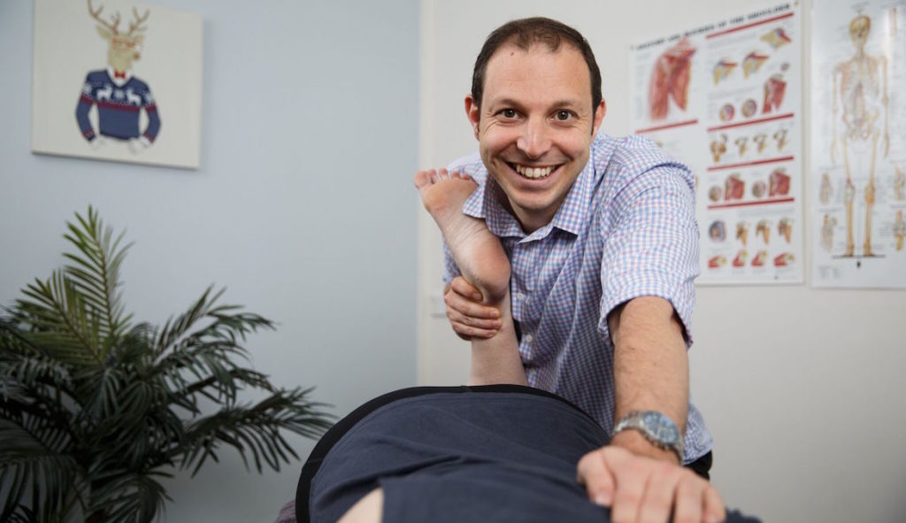 Physiotherapist Alex Donald assessing and treating knee pain in a patient.